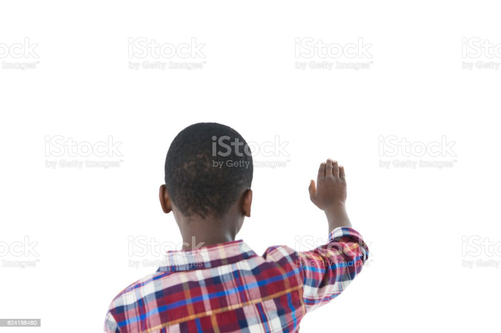 Boy pretending to touch an invisible screen against white background stock photo