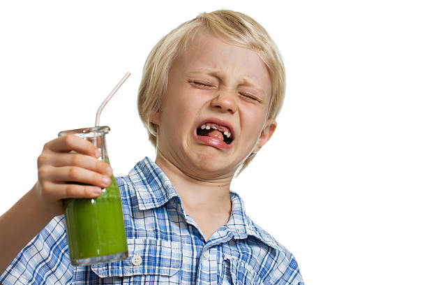 Boy pulling funny face holding green smoothie stock photo