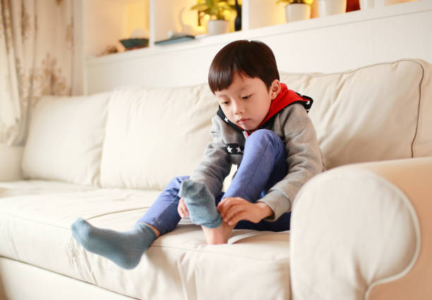 Boy pulling on socks stock photo