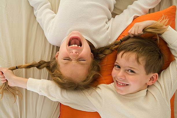 Boy pulling sister's pigtails stock photo