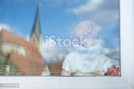 Boy puppet with mouthguard standing behind window