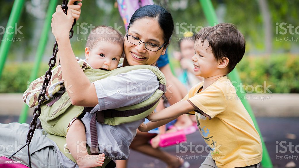 Boy pushes his mother and baby brother on a swing stock photo