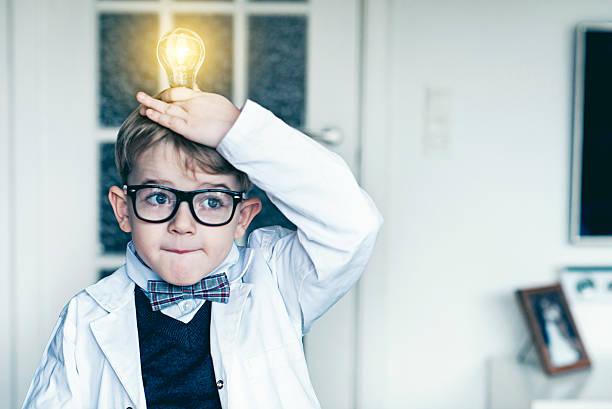 Jungen steht Glühbirne über dem Kopf und mit der Idee – Foto