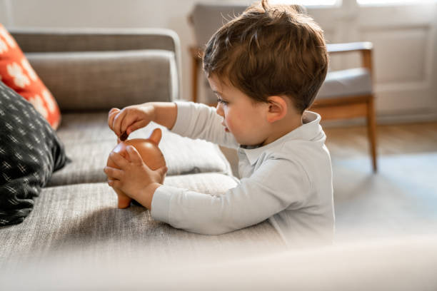 Boy putting coins on piggy bank stock photo