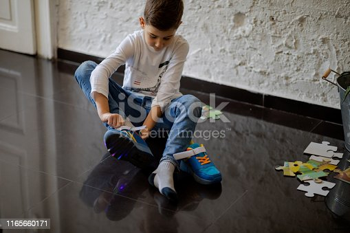 Boy sitting on the floor at home and putting on sports shoes