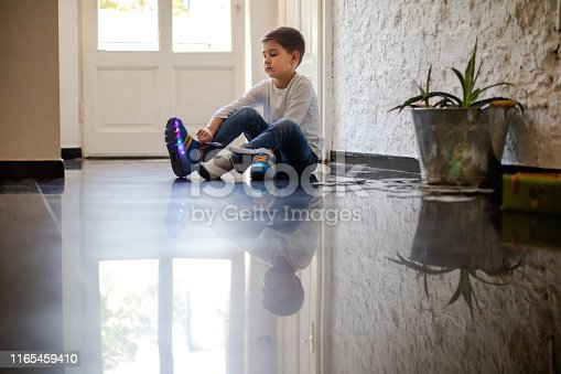 Boy sitting on the floor at home and putting on sports shoes with LED illumination