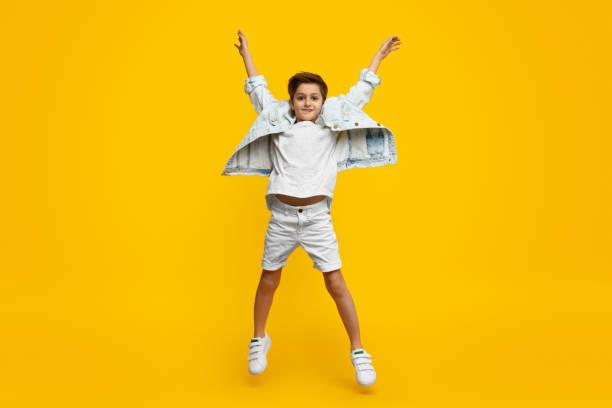 Boy raising hands and jumping stock photo