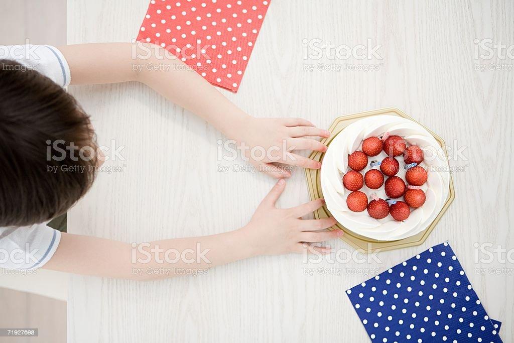 Boy reaching for cake royalty-free stock photo