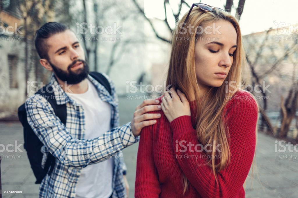 Boy reaching out and touching his girlfriend on the shoulder Girl looking away with irritation and turning back to her boyfriend Adult Stock Photo