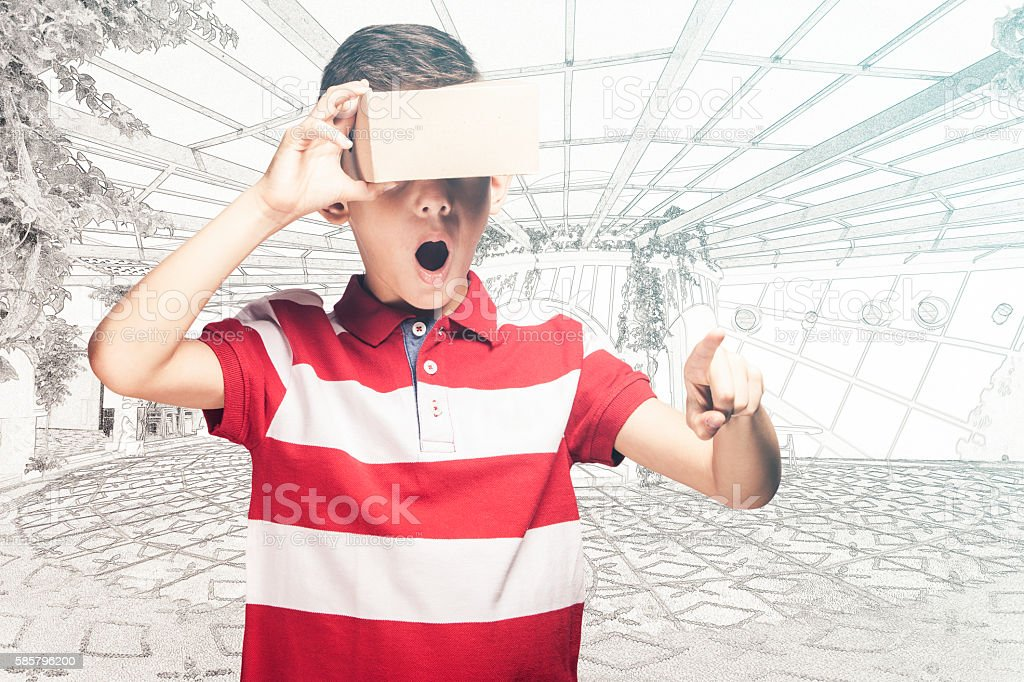 Boy reacts while wearing virtual reality headset stock photo