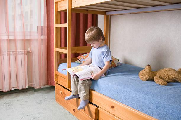 junge liest ein buch auf etagenbett - etagenbett weiss stock-fotos und bilder