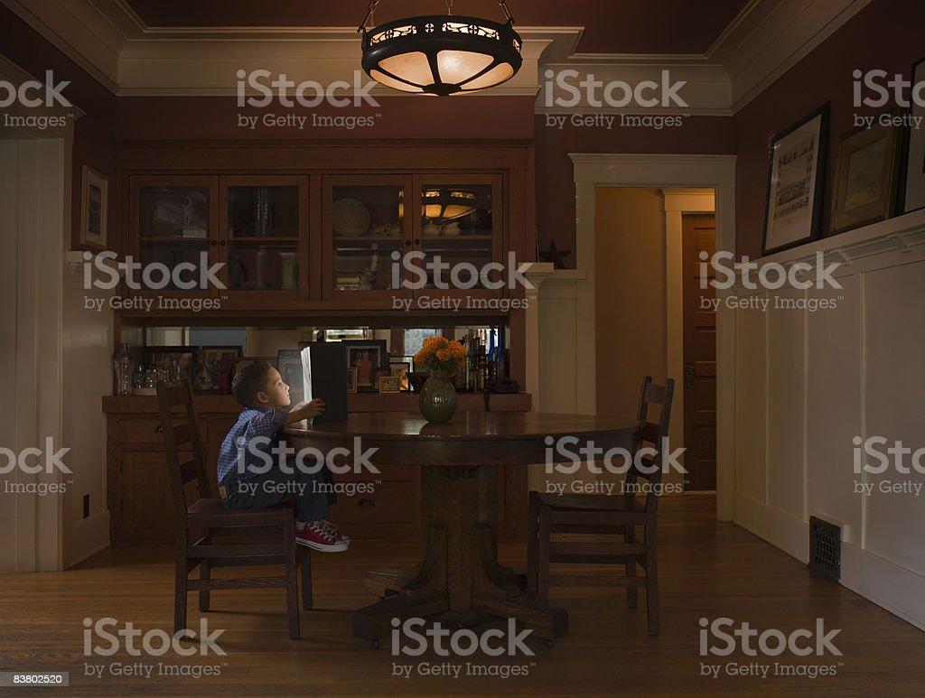 Petit garçon lecture livre avec lumière de départ photo libre de droits