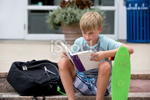 istock Boy reading on school steps 503701595