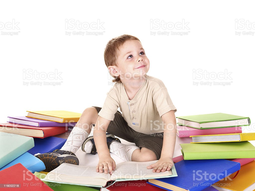 Boy reading pile of books. stock photo