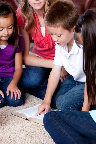 junge liest die bibel - lila mädchen zimmer stock-fotos und bilder