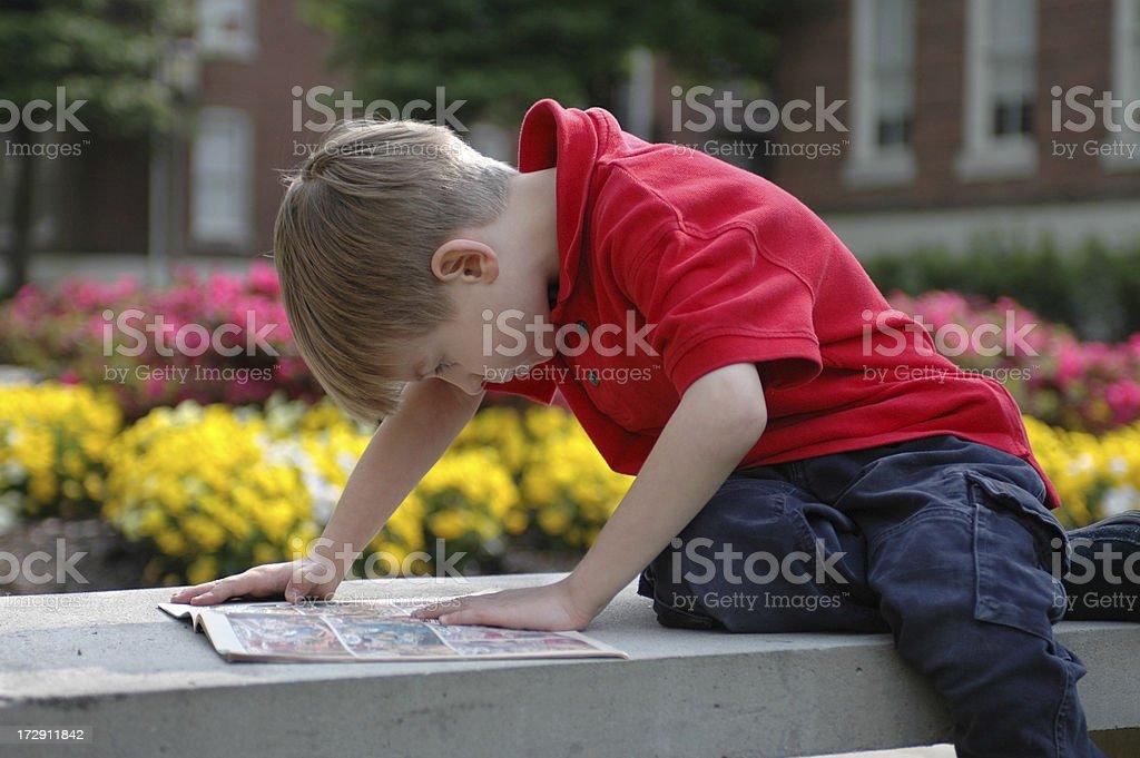 Boy Reads Outside stock photo