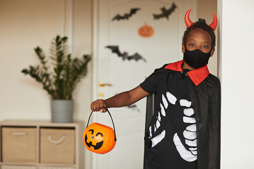 Portrait of cute African American boy wearing spooky devil costume with red horns and mask holding jack o' lantern basket for candies looking at camera