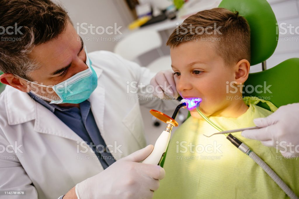 Boy receiving dental filling drying procedure