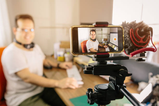 Boy recording content with his mobile phone for online courses or online training. Use an external microphone to make it easier to hear. At home