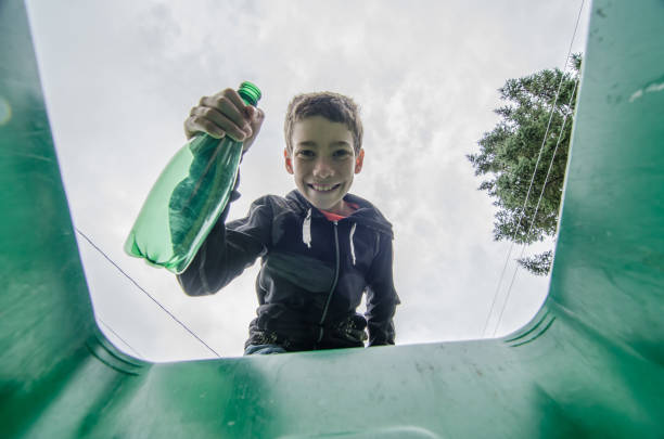 Boy recycling plastic bottle Boy recycling plastic bottle in a home container bottle bank stock pictures, royalty-free photos & images