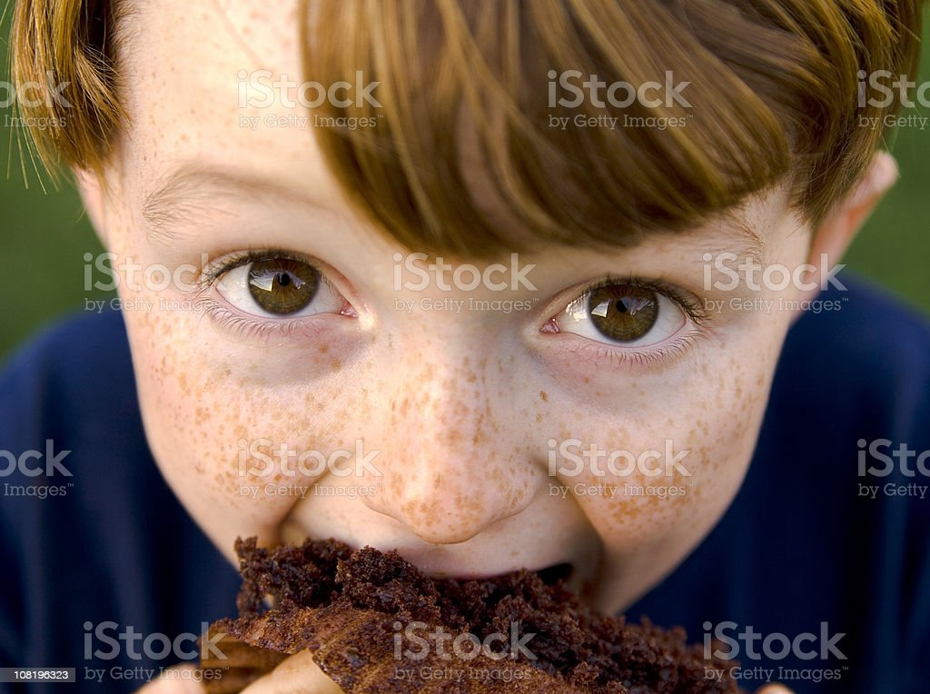 Boy Redhead & Funny Freckle Face Child Eating Unhealthy Chocolate Cupcake stock photo