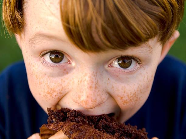 junge redhead. & lustiger sommersprosse gesicht kind isst ungesund schokolade cupcake - kinderschokolade stock-fotos und bilder
