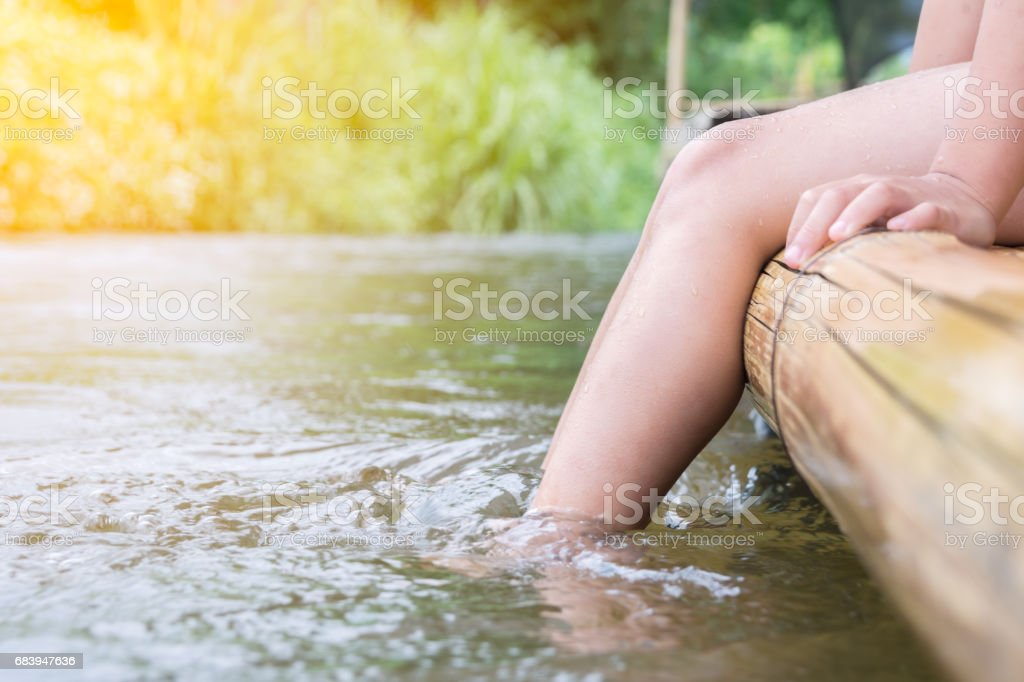 boy relaxing and sitting on bamboo raft at river with sunlight stock photo