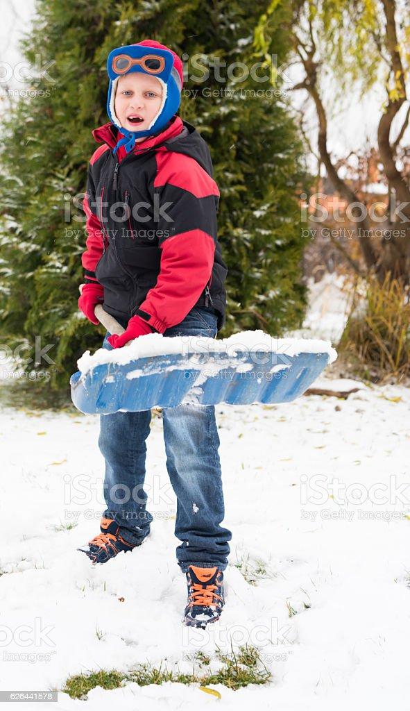 Boy removes snow shovel in the winter stock photo