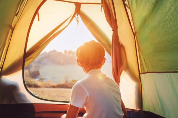 Niño descansar en tienda de campaña y disfrutar con luz de puesta de sol en el valle de la montaña - foto de stock