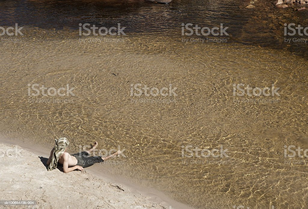 Boy (12-13) resting by stream, elevated view royalty-free stock photo
