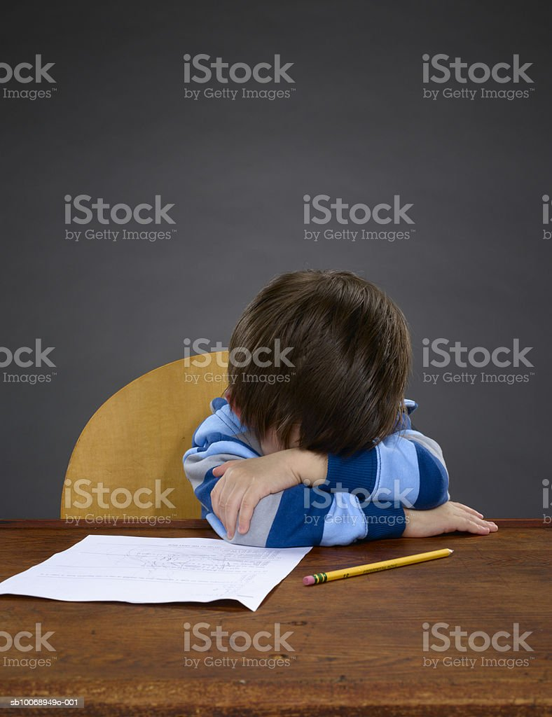 Boy (2-3) resting on table foto de stock libre de derechos