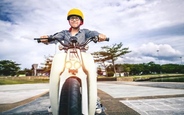 garçon d'équitation un vélo - moped photos et images de collection