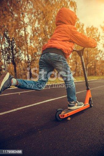 Little boy riding a scooter outdoors
