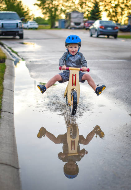 Junge Reiten Fahrrad durch Pfütze – Foto