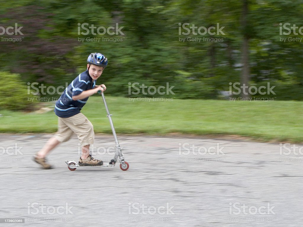 Boy Riding Fast On Scooter With Helmet Looking At Camera royalty-free stock photo