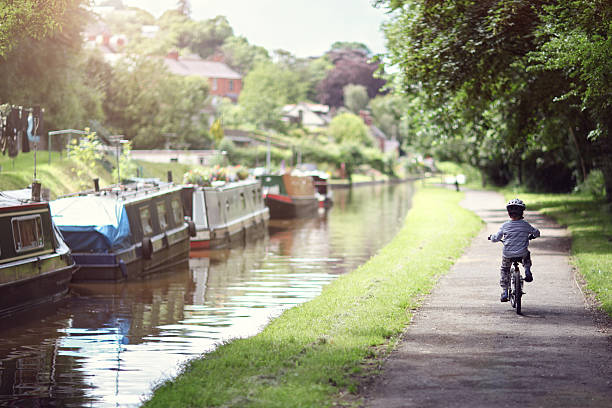 Boy riding his bike Riding a bicycle on a tow path by a canal concept for healthy lifestyle, exercising and vacations canal stock pictures, royalty-free photos & images
