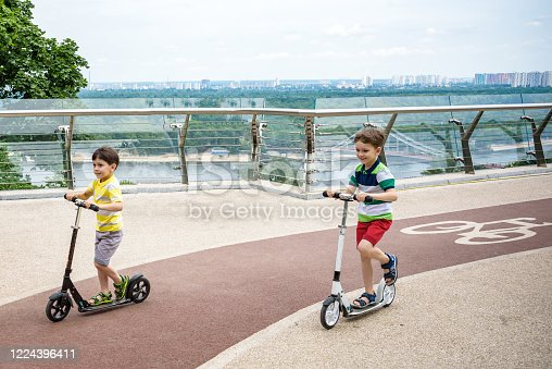 Two boy kids riding his scooter in the local park new glass bridge. Sunny summer day. Tourism concept.