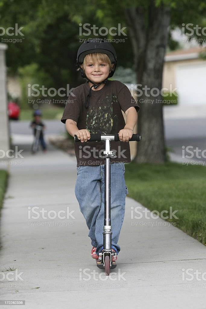 Boy Riding His Scooter royalty-free stock photo