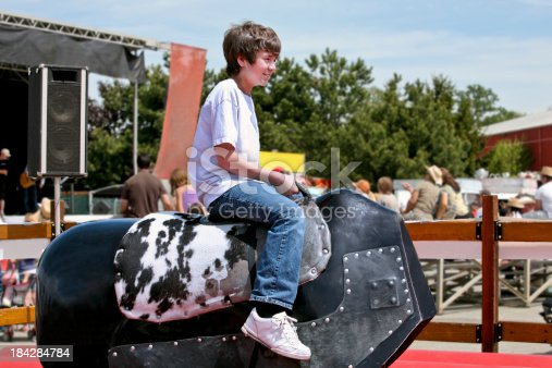 Boy tries to stay on the Mechanical Bull at a Rodeo.