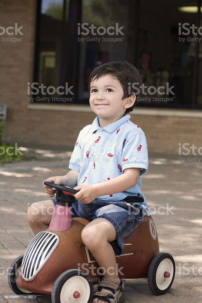 Boy (4-5) riding old fashioned toy, smiling foto de stock royalty-free