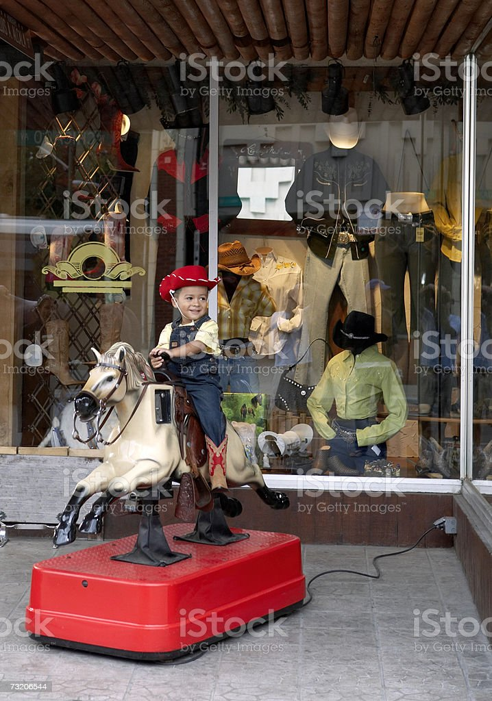Boy (2-4) riding on coin operated horse outside store stock photo