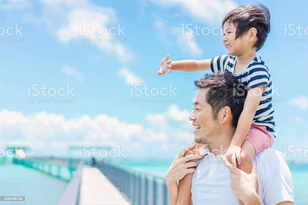 Boy riding on father's shoulders stock photo