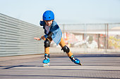 Portrait of preteen boy riding fast on roller skates at outdoor skate park in summer