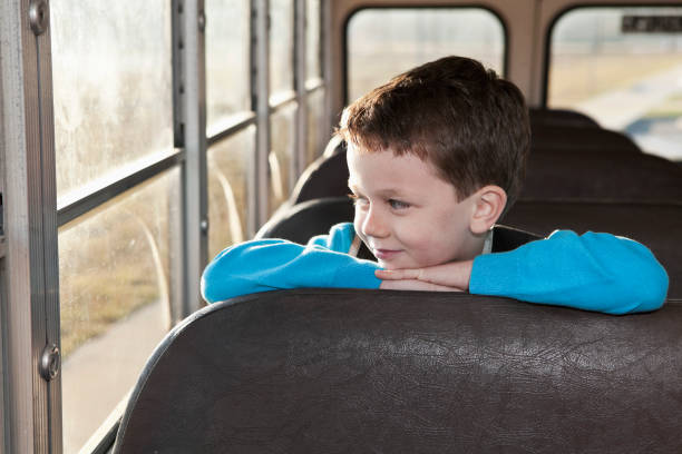 boy riding school bus - boy looking out window stock pictures, royalty-free photos & images