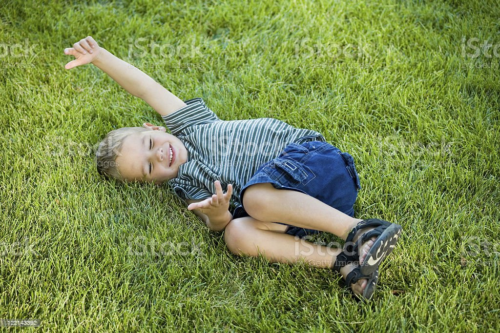 Boy Rolling in Grass royalty-free stock photo