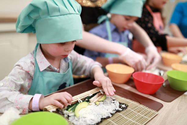Estera rodante Boy sobre sushi - foto de stock