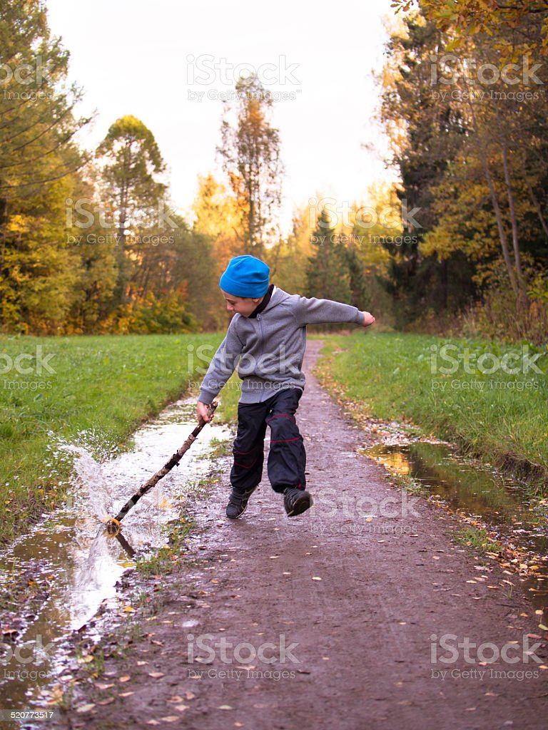 Boy running along the path and strikes stick on puddle stock photo