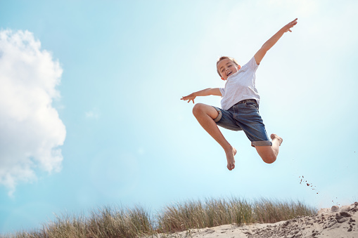 Boy running and jumping over sand dune on beach vacation