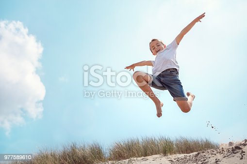 Boy leaping and jumping over sand dune on beach vacation