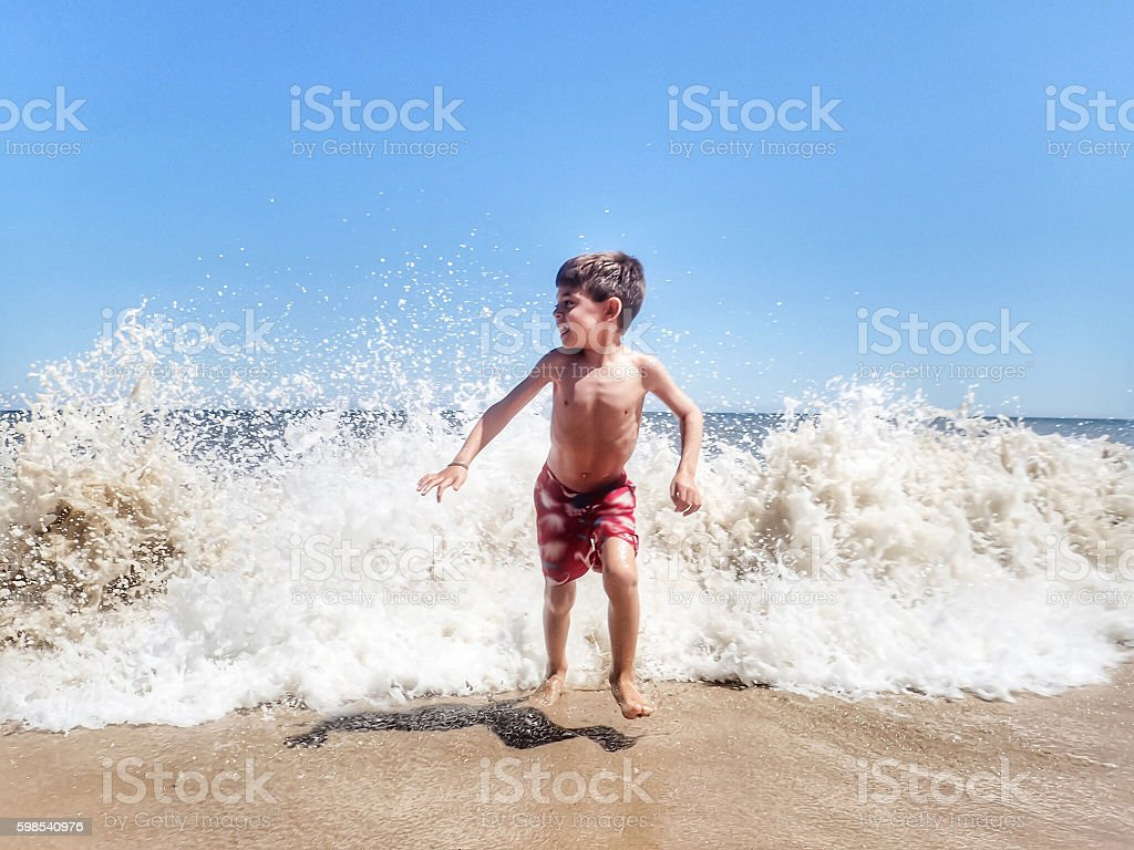 Boy running from breaking wave stock photo